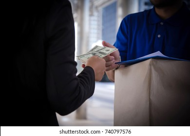 Delivery man receive paying cash payment Package courier parcel, people hand giving courier service payment. customer girl receiving register package postal box, checkout payout US dollar note money.