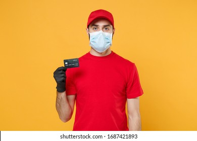 Delivery man red cap blank t-shirt uniform mask gloves isolated on yellow background studio Guy employee work courier hold credit card Service quarantine pandemic coronavirus virus 2019-ncov concept