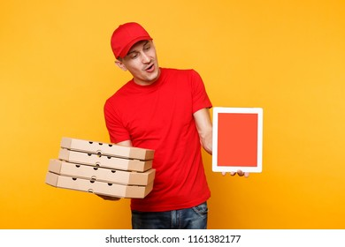 Delivery man in red cap t-shirt giving food order pizza in flatbox boxes on yellow background. Male employee pizzaman courier hold tablet pc computer with blank empty screen mockup. Service concept