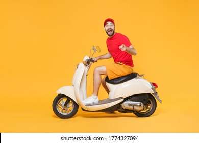 Delivery man in red cap t-shirt uniform driving moped motorbike scooter isolated on yellow background studio Guy employee working courier Service quarantine pandemic coronavirus virus covid19 concept