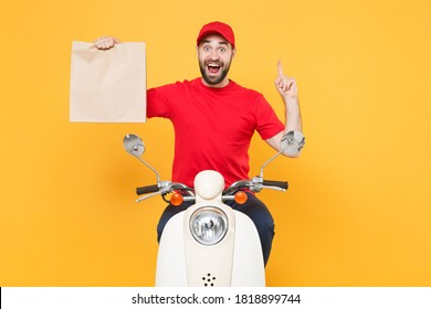 Delivery man in red cap t-shirt uniform driving moped motorbike scooter hold craft paper packet with food isolated on yellow background studio male employee working courier Service quarantine concept.