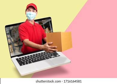 delivery man in red shirt with hygienic mask, holding goods order in package parcel out from laptop computer with warehouse background. order online, delivery service on covid-19 coronavirus epidemic