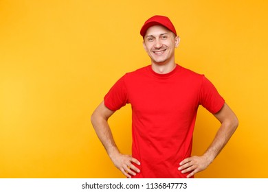 Delivery man in red uniform isolated on yellow orange background. Professional smiling male employee in cap, t-shirt working as courier or dealer standing with arms akimbo. Service concept.