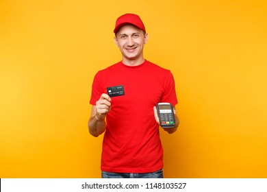 Delivery man in red uniform isolated on yellow background. Male employee in cap, t-shirt courier holding wireless modern bank payment terminal to process and acquire credit card payments, black card