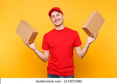 Delivery man in red uniform isolated on yellow orange background. Professional male employee courier dealer in cap t-shirt holding empty cardboard boxes. Receiving package service concept. Copy space