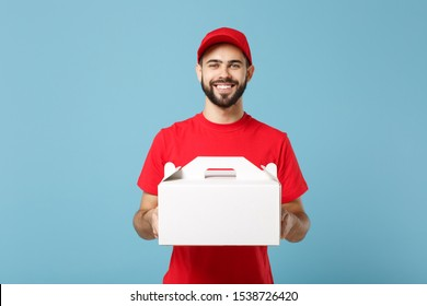 Delivery man in red uniform isolated on blue background, studio portrait. Male employee in cap t-shirt print courier hold cake dessert in unmarked cardboard box. Service concept. Mock up copy space