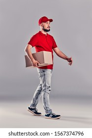 Delivery man in red uniform isolated on gray background, studio portrait. Male employee in cap t-shirt print working as courier dealer hold empty cardboard box. Service concept. Mock up copy space