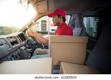 Delivery man in red uniform in van