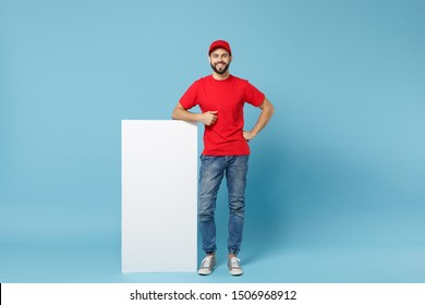 Delivery man in red workwear hold big white empty billboard isolated on blue background, studio portrait. Male employee in cap t-shirt working as courier dealer. Service concept. Mock up copy space
