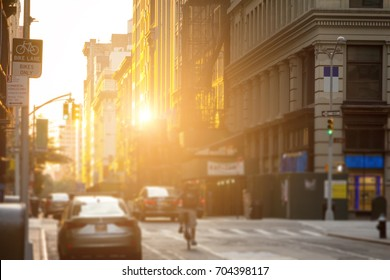 Delivery man rides bike down the streets of New York City with the sunshine reflecting off the downtown building windows