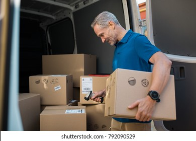 Delivery man scanning cardboard boxes with barcode scanner. Courier holding parcel and scanning barcode with barcode reader in van. Mature man reading and scanning labels on boxes before shipment.