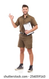 Delivery man showing ok sign. Happy courier holding a clipboard under the arm and showing ok sign. Full length studio shot isolated on white.