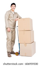 Delivery man standing beside luggage trolley with cardboard boxes on white background