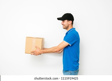 delivery man standing in profile and offering the mail, or package cardbox, to someone, on white background