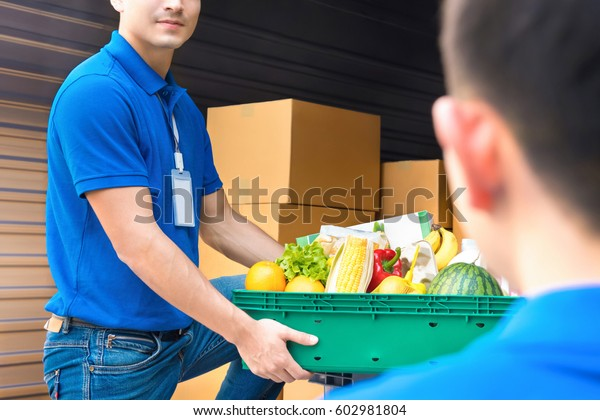 Delivery man taking food basket from the car delivering to customer - grocery shopping service concept