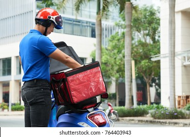 Delivery man taking food out of bag on his scooter