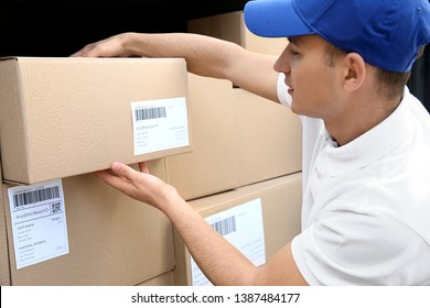 Delivery man taking parcel from car outdoors