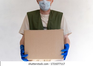 Delivery man in uniform. Holds a cardboard box in medical protective gloves and a mask. Fast and free delivery of transport. Online shopping and express delivery.
