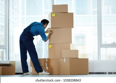 Delivery man in uniform sticking notepapers with numbers on packed boxes before loading