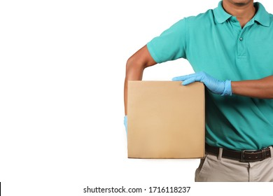 Delivery man wearing green shirts holding cardboard boxes on his side in medical rubber gloves. Online shopping and Express delivery concept.