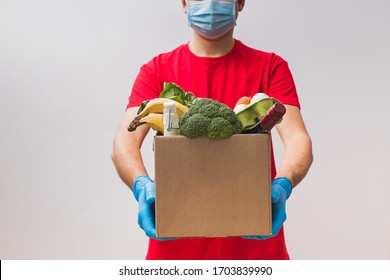 Delivery man wearing mask and gloves holding box full of different groceries. Order food online, delivery during quarantine