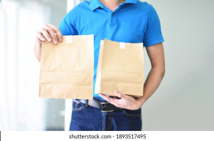 Delivery man wearing protective face mask coronavirus and hand holding craft paper food packaging bag service, Postman express for takeaway food delivery service to home - selective focus