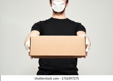 Delivery man wearing a protective mask and medical gloves holds the box in front of him on an isolated white background. Safe delivery. On an isolated white background.