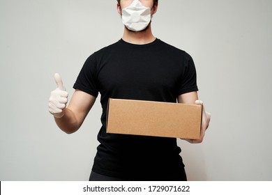 Delivery man wearing a protective mask and medical gloves holds the box and gives a thumbs up against an isolated white background
