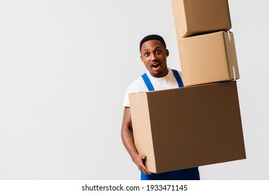 A delivery man wearing a white T-shirt and blue pants holds boxes in his hands. Isolated on a white background. Concept of delivery, mail, shipment, loader, courier. Box close up. Sign language