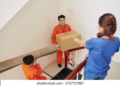 Delivery men carrying carpet and box upstairs, unrecognizable woman standing there telling them where to go, vertical high angle shot