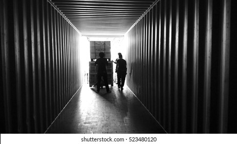 Delivery men are loading cargo boxes into a container . Multiple exposure, black and white