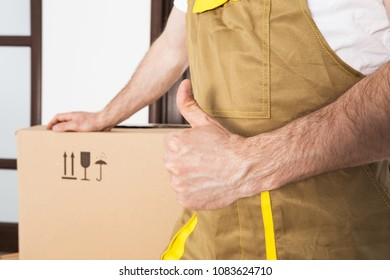 Delivery and moving goods service background. Mover hand with thumb up close-up.