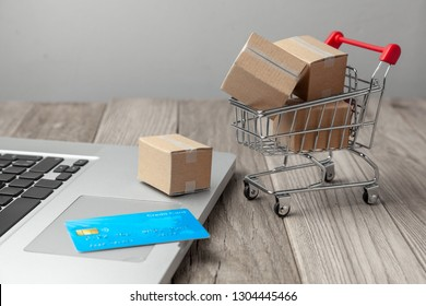 Delivery of the order from the online store. Shopping with payment online. Boxes with goods in shopping basket with a credit card on the table with laptop.