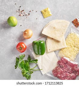 Delivery of packaged food for dinner. meat and cheese in plactic bag green pepper, tortilia, lime, tomato