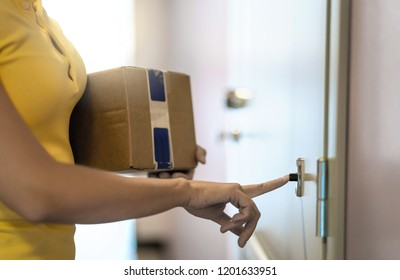 Delivery person delivering package to home door. Shipment service. Woman ringing doorbell. Female courier working and holding carton box in building. Girl shipping online order to customer's house.