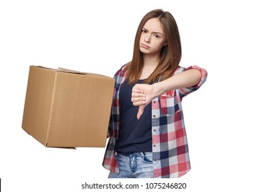 Delivery, relocation and unpacking. Discontent young woman holding cardboard box and gesturing thumb down, isolated on white background