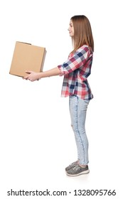 Delivery, relocation and unpacking. Full length smiling young woman giving cardboard box, side view portrait