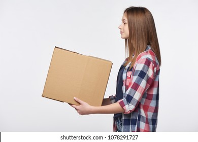 Delivery, relocation and unpacking. Side view portrait of woman giving cardboard box looking forward at blank copy space, isolated