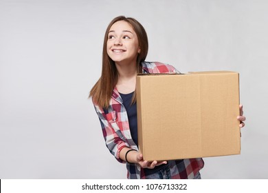 Delivery, relocation and unpacking. Smiling young woman holding cardboard box, looking at blank copy space to the side, isolated