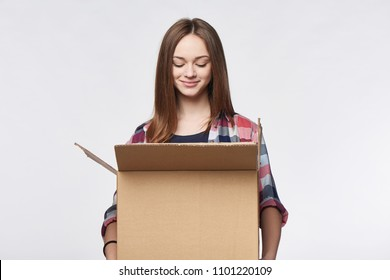 Delivery, relocation and unpacking. Smiling young woman holding carton box looking in box
