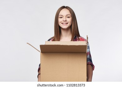 Delivery, relocation and unpacking. Smiling young woman holding carton box looking at camera