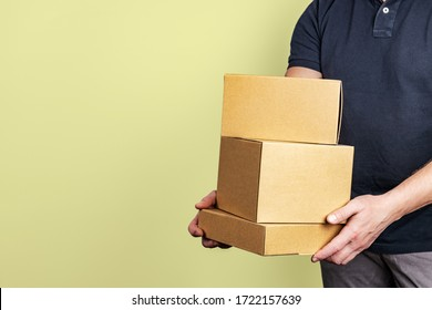 Delivery service by courier with parcels in hand on a light gray background, shallow depth of field, selective focus.