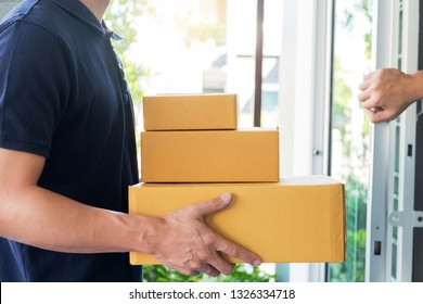 delivery service concept, customer hand receiving a cardboard boxes parcel from delivery man at home