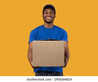 Delivery Service Concept. Smiling black mailman wearing blue cap and t-shirt holding cardboard box, showing and giving it to camera, copy space. Postal worker standing on orange studio background