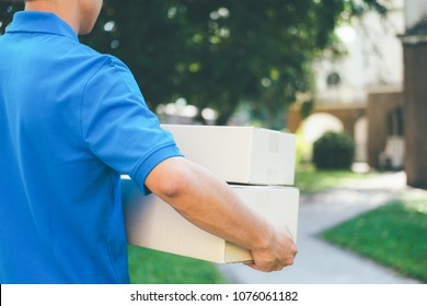 Delivery service courier standing in front of the house with boxes and clipboard in hands.
