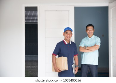 delivery service male and customer smiling to camera at home