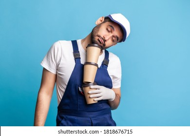 Delivery service. Tired inefficient courier man in overalls lying on coffee cups and sleeping, feeling exhausted bored after stressful night shift. Laziness at work and lack of energy, need caffeine