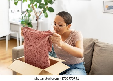 delivery, shipping and people concept - happy young african american woman opening parcel box with clothes at home