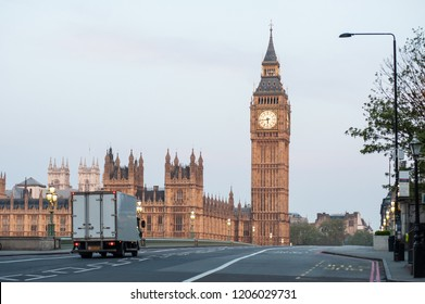 A delivery truck crosses Westminster Bridge at dawn in London. Big Ben and the Houses of Parliament. No traffic, no people. Early morning.