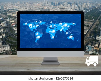 Delivery truck icon with connection line and world map on computer screen on table over city tower, street, and expressway, Transportation online concept, Elements of this image furnished by NASA